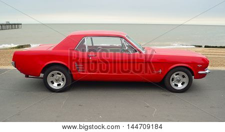 FELIXSTOWE, SUFFOLK, ENGLAND - AUGUST 27, 2016: Classic Red Ford Mustang parked on seafront promenade.