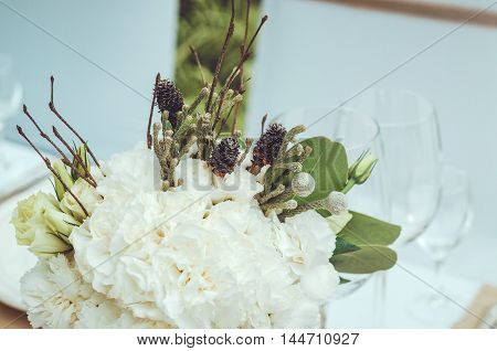 Beautiful white bouquet of carnations cones roses flowers in vase on table craft background. Winter wedding event floral decoration. Twin flower. Text copy space.