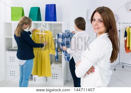Young self-employed woman in the background two women watching clothes at fashion boutique