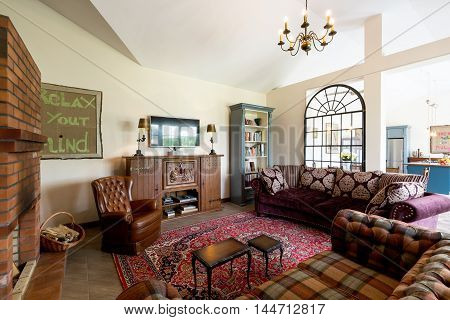 Spacious living room interior in cottage style with checked sofas leather armchair fireplace chest of drawers and the chandelier