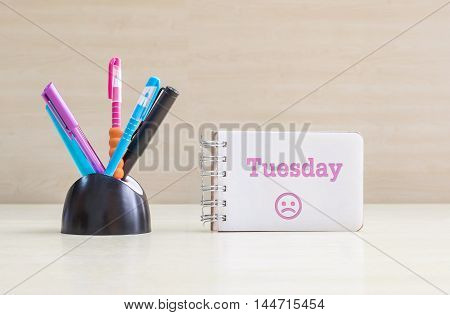 Closeup color pen with black ceramic desk tidy for pen and pink tuesday word in white page and frown face emotion at the note book on blurred wood desk and wood wall textured background