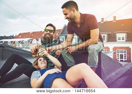 Three young adults enjoying each others company while drinking beer and talking on roof in Europe