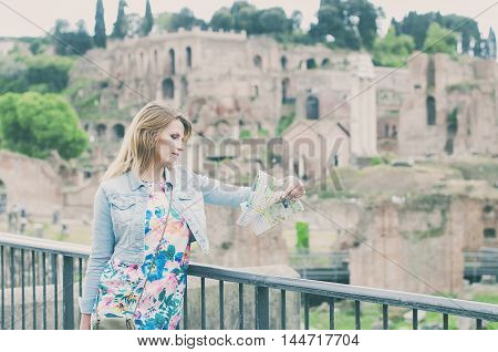 Pretty Female Tourist Looking A Map On The Ruins Of The Roman Forum In Rome, Italy
