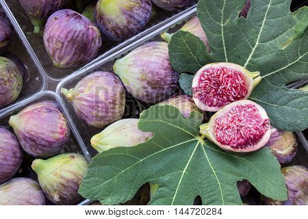 Cut figs on a fig leaf on a background of whole figs in the boxes for sale. Ripe figs in boxes for sale in the greek market. Horizontal. Top view.