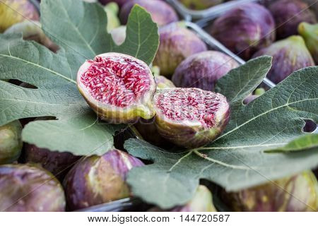 Cut figs on a fig leaf on a background of whole figs in the boxes for sale. Ripe figs in boxes for sale in the greek market. Horizontal. Close.