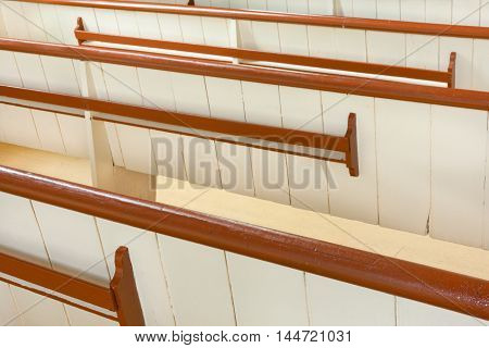 View from behind of wooden church pews.