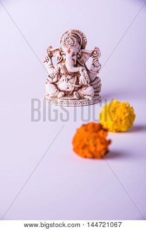 statue of Ganesha Idol made of white marbal on plain bright red background. Clear space for text or headline