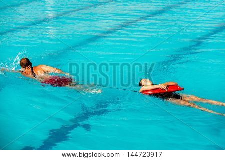 Lifeguard training - lifeguard pulling victim to safety using floating rescue buoy