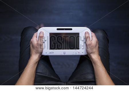 Gothenburg, Sweden - August 29, 2016: A shot from above of a young mans hands holding a white game pad for the WiiU video game console developed by Nintendo Co., Ltd.