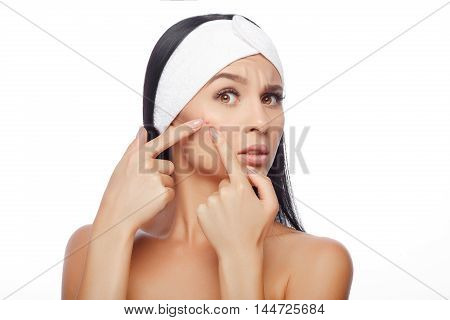 Young woman squeezing her pimple, removing pimple from her face. Woman skin care concept. Acne spot pimple spot skincare beauty care girl pressing on skin problem face.