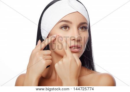 Young woman squeezing her pimple, removing pimple from her face. Woman skin care concept. Acne spot pimple spot skincare beauty care girl pressing on skin problem face. poster