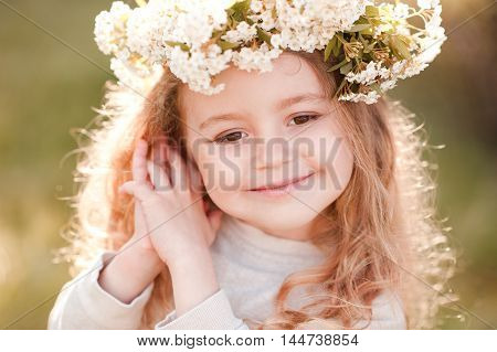 Smiling baby girl 4-5 year old wearing flower headband in sunny light outdoors. Summer portrait of child. Posing over green nature background.