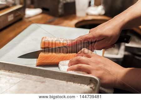 Sushi chef cuts raw fish before service.