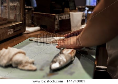 Sushi chef prepares fish for dinner service.