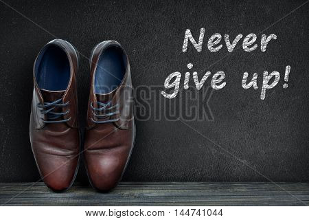 Never give up text on black board and business shoes on wooden floor