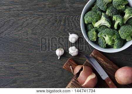 A bowl with fresh broccoli, cloves of garlic and potatoes on dark wooden background. Brocoli soup ingredients.