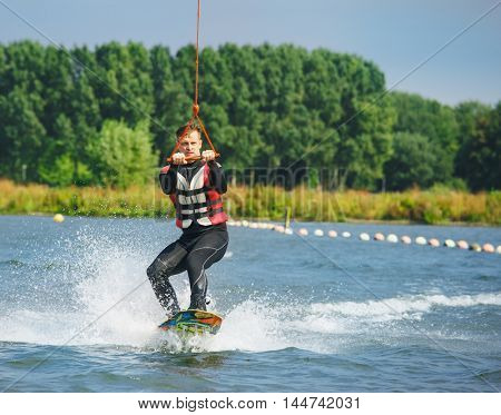 Wakeboarder in a swimsuit and life jacket being cable towed