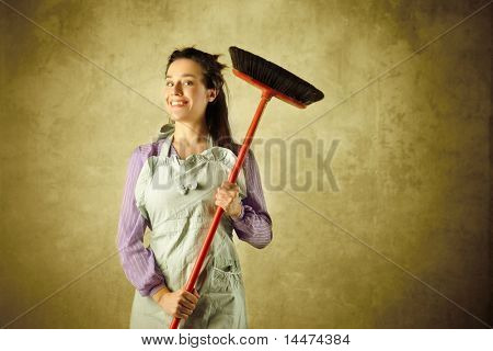 Smiling housewife holding a broom