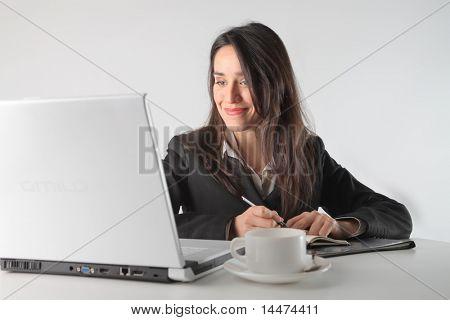 Sonriendo empresaria trabajando delante de un ordenador portátil