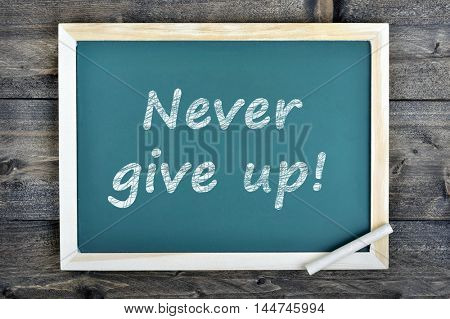 Never give up text on school board and chalk on wooden table