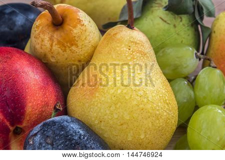 a few fresh bio pears grapes plums and nectarine on the wooden table
