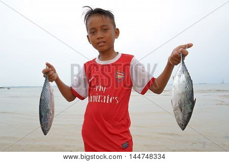 Labuan,Malaysia-Aug 28,2016:Unidentified kid of traditional fisherman showing of the fish catch of the day at Kiansam beach on 28th Aug 2016 at Labuan Pearl Of Borneo,Malaysia.