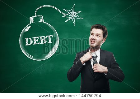 Debt concept with choking businessman and sketch on chalkboard background