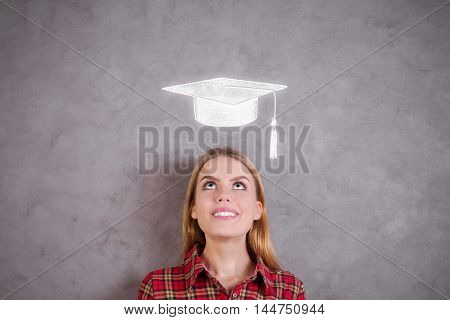 Portrait of attractive young woman looking up at mortarboard sketch on concrete wall. Graduation concept