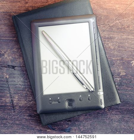 Black ereader with notebook in leather cover and ink pen on vintage old rustic wooden table. Blank E-book reader. New technologies in education. Back to school concept. Top view.
