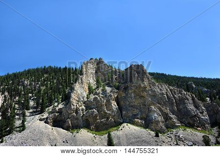 Rugged crevices and ridges rise out of the Gallatin Mountain Range in Montana. Sunny blue sky above.
