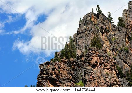 Rugged ridge of a mountain in Yellowstone National Park is framed by blue sky and clouds.
