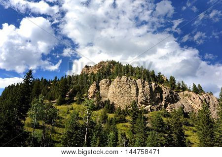 Ridge on top of a mountain in the Absaroka Mountain range is rugged and steep. Landscape image is complete with fluffy white clouds and blue sky.