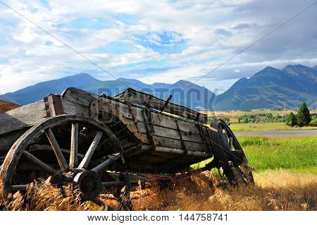 Broken down wooden wagon sits overgrown with weeds. It has a view of distant Absaroka Mountains in Paradise Valley Wyoming.