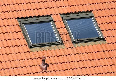 Classic garrets on a red tile roof.