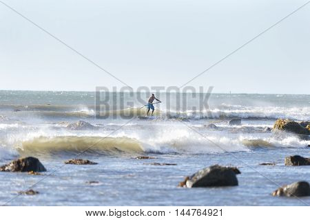 Westport Massachusetts USA - July 5 2014: Stand up paddleboarder off Gooseberry Neck negotiates rocky shoreline in small surf