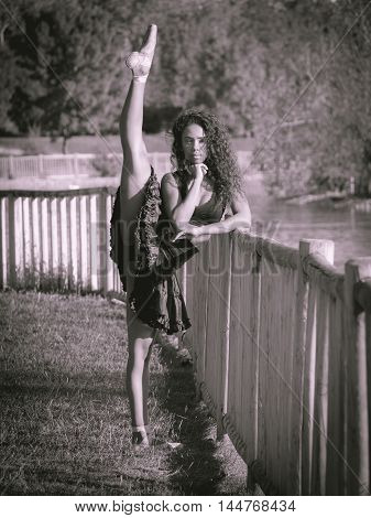 very flexible Latino dancer with black clothes dancing in a park Monochrome