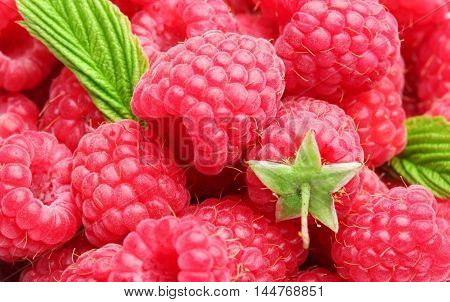 Raspberries with green leaves in the center