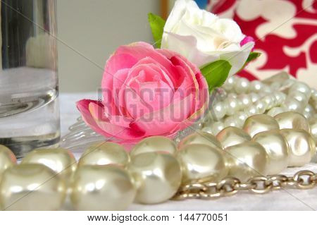 Pink rose among pearls and feminine jewellery