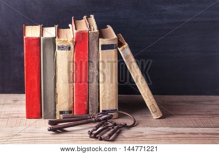 Stack of old vintage books and a bunch of old big iron keys lie on a wooden table.