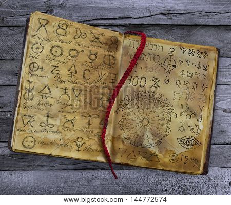 Old witch book with alchemic symbols lying on the wooden table. Halloween still life, black magic ritual with mysterious occult and esoteric signs