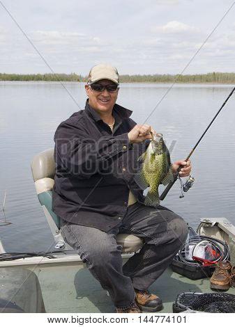 A fisherman with a large Black Crappie