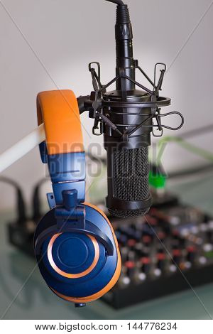 Condenser Microphone with headphones in the studio, behind the mixer getting ready to record live.