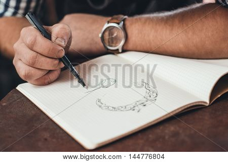 Closeup of a jeweler leaning on a bench sketching out new jewelry designs in a notebook while working in his shop