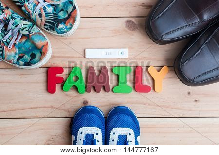 The Shoes For The Entire Family And New Member With Family Alphabet On The Wooden Floor