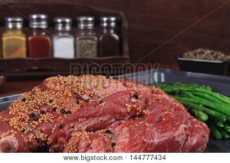 meat raw beef fillet chunk on black tray asparagus on wooden table allspice pink white black green peppercorn