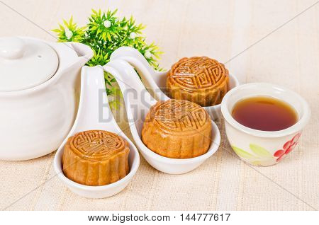 Mooncake and tea Chinese mid autumn festival food on tablecloth.