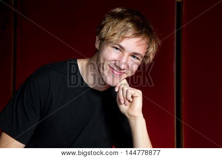 A disheveled teen boy leans on his fist. He is in front of a red background in a horizontal portrait.