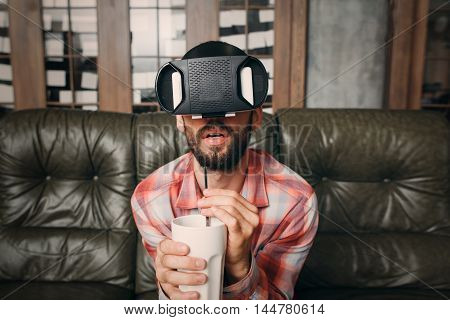 Man watching exciting movie in vr goggles. Bearded guy in virtual reality headset forgot about drinking while watching 3d video. Cinema at home, innovation, entertainment concept