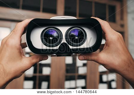Virtual reality glasses with image inside. Hands holding vr goggles with picture of movie to watch. Modern technology, innovation, cyberspace, entertainment concept