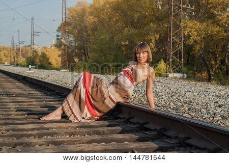 Beautiful Girl Sitting On Railroad Track.